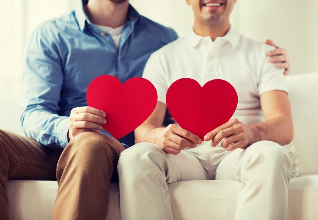 people, homosexuality, same-sex marriage, valentines day and love concept - close up of happy gay male couple with red hearts at home