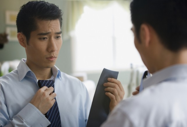 Korean businessman choosing tie in mirror