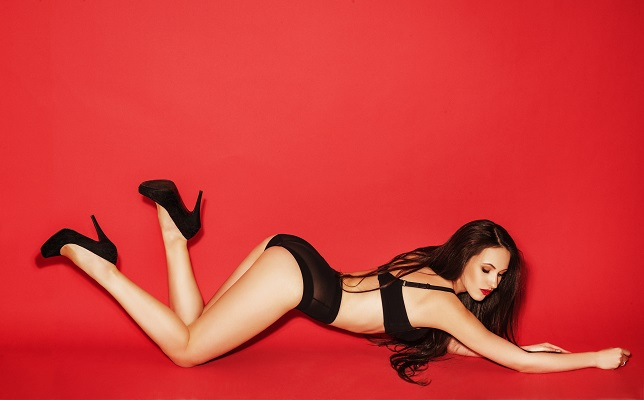 Gorgeous woman with long brown hair in retro black lingerie, posing on red background.