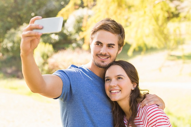 Cute couple doing selfie in the park on a sunny day