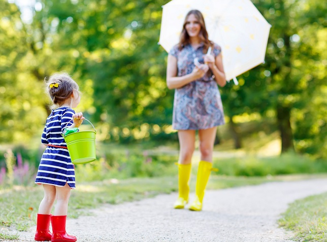 Mum and her little adorable kid daughter in rain boots, playing together in summer sunny park, on warm day.