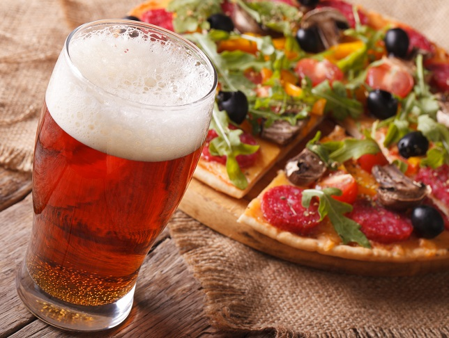 Cold beer and hot pizza with arugula on the table close-up horizontal. rustic style
