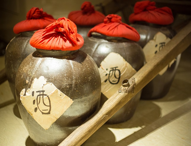 Row of ancient chinese jugs inside with the chinese character for alcohol written on the outside