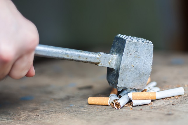 Quit smoking, human hand breaking cigarettes with hammer